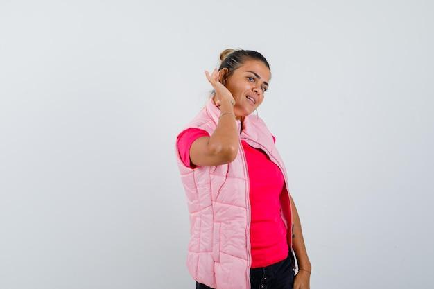 Mulher jovem segurando as mãos perto da orelha para ouvir algo em uma camiseta e jaqueta rosa e parece curiosa