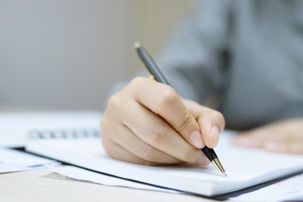 Mulher jovem segurando as páginas do caderno abertas com lápis azul em uma mesa de madeira clara com marcadores