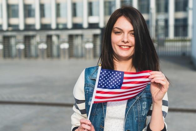 Mulher jovem, segurando, bandeira americana, ligado, dia independência