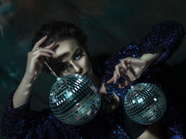 Mulher jovem, segurando bola discoteca