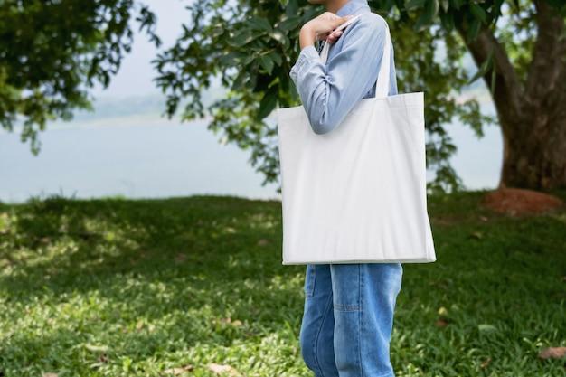 Mulher jovem, segurando, bolsa algodão, em, experiência verde