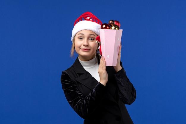 Mulher jovem segurando brinquedos de árvore no fundo azul emoção no feriado de ano novo