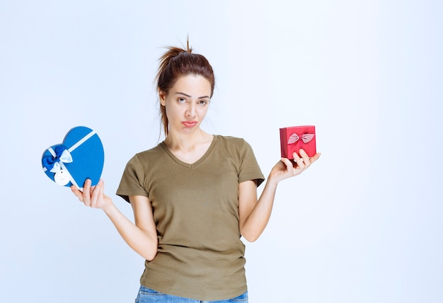 Mulher jovem segurando caixas de presente em formato de coração vermelho e azul e parece confusa por ter feito a escolha