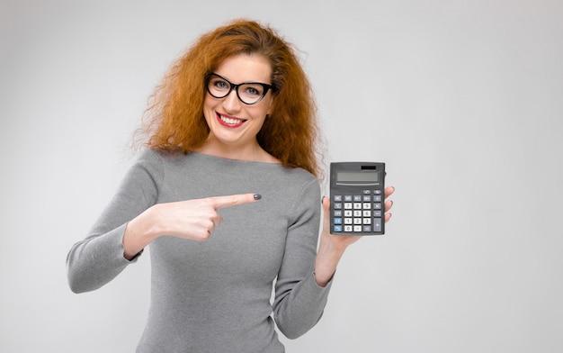 Mulher jovem, segurando, calculadora