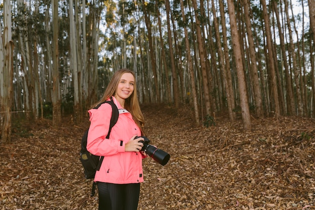 Mulher jovem, segurando, câmera, em, floresta