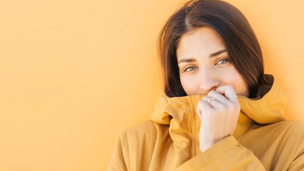 Mulher jovem, segurando, casaco amarelo, frente, dela, boca, olhando câmera