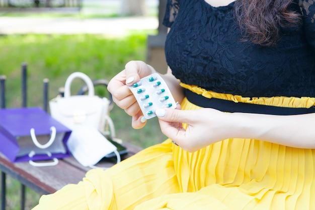 Mulher jovem segurando comprimidos no parque