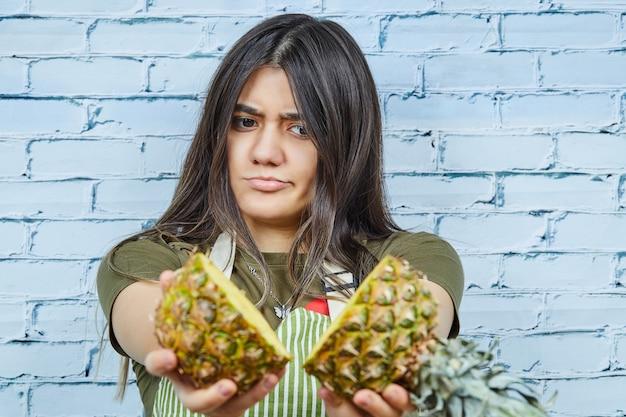 Mulher jovem segurando duas metades de abacaxi em fundo azul