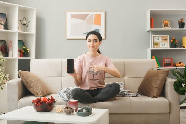 Mulher jovem segurando e apontando para o telefone sentada no sofá atrás da mesa de centro na sala de estar