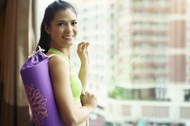 Mulher jovem, segurando, esteira yoga, e, levantar, espelho, predios, fundo