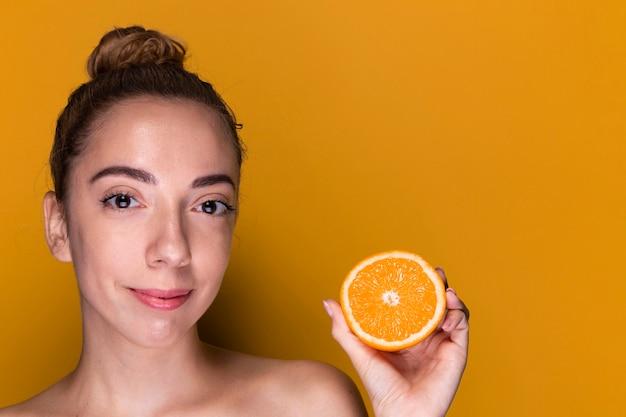 Mulher jovem, segurando, fatia laranja