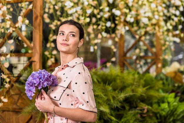 Mulher jovem, segurando, flor azul, em, casa verde