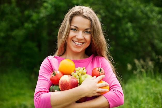 Mulher jovem segurando frutas e vegetais