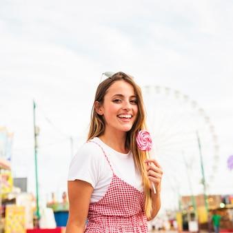 Mulher jovem, segurando, grande, pirulito, em, parque divertimento