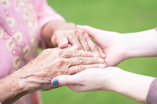 Mulher jovem, segurando, idoso, mão