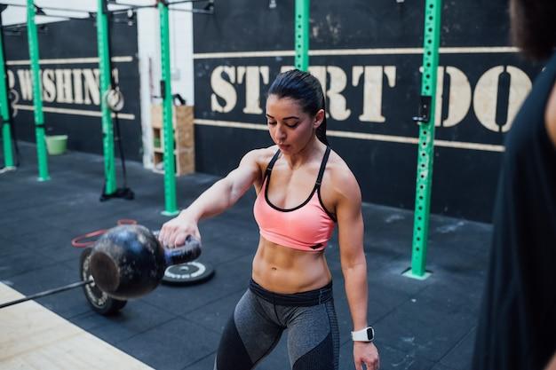 Mulher jovem, segurando, kettlebell, ginásio indoor, treino