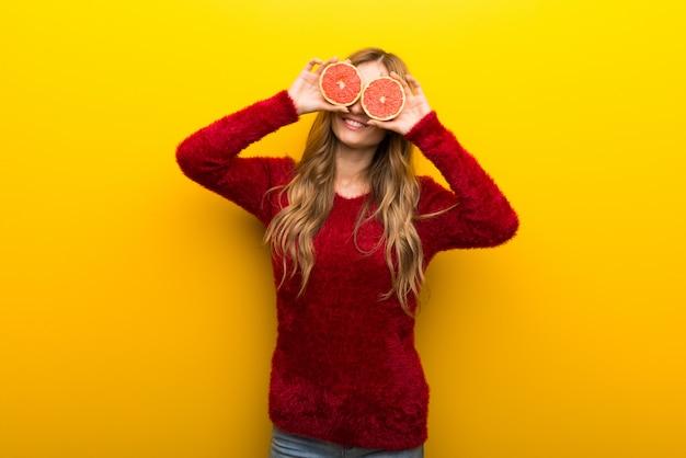 Mulher jovem, segurando, laranja, fatias, ligado, vibrante, experiência amarela