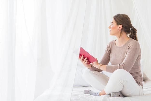 Mulher jovem, segurando, livro, sentar cama