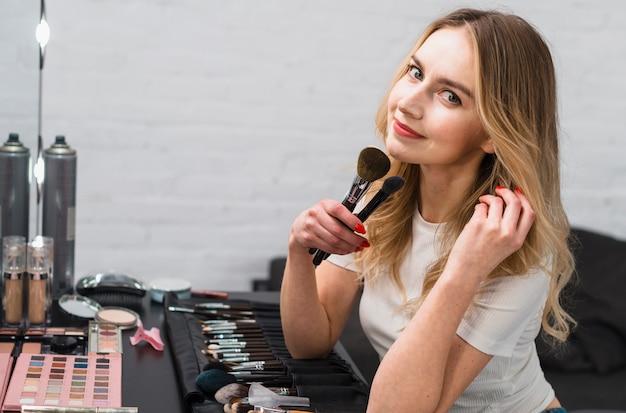 Mulher jovem, segurando, maquiagem, escovas, sentando, em, estúdio