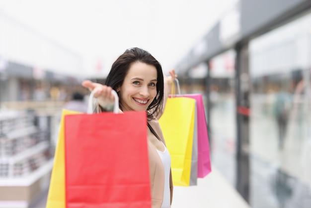 Mulher jovem segurando muitas sacolas multicoloridas na loja