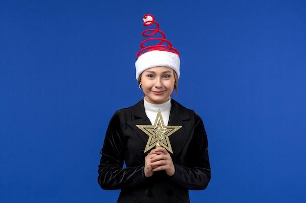 Mulher jovem segurando o brinquedo estrela de frente na cor de fundo azul, ano novo, mulher, feriado