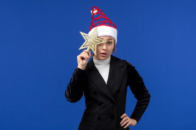 Mulher jovem segurando o brinquedo estrela de frente na cor de fundo azul, ano novo, mulher, férias