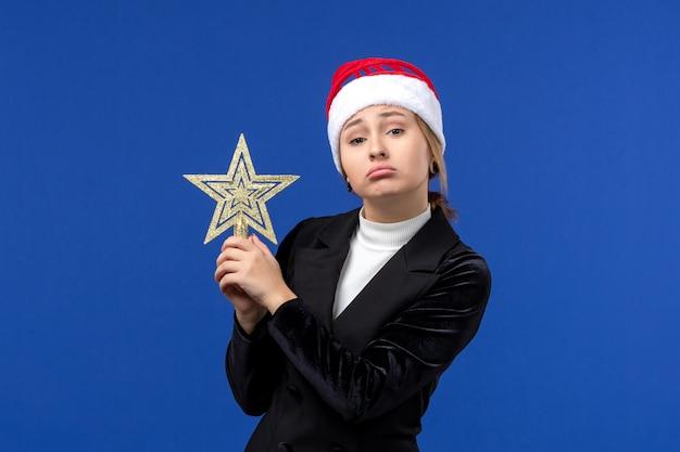 Mulher jovem segurando o brinquedo estrela na mesa de cor azul, mulher, de frente, no feriado