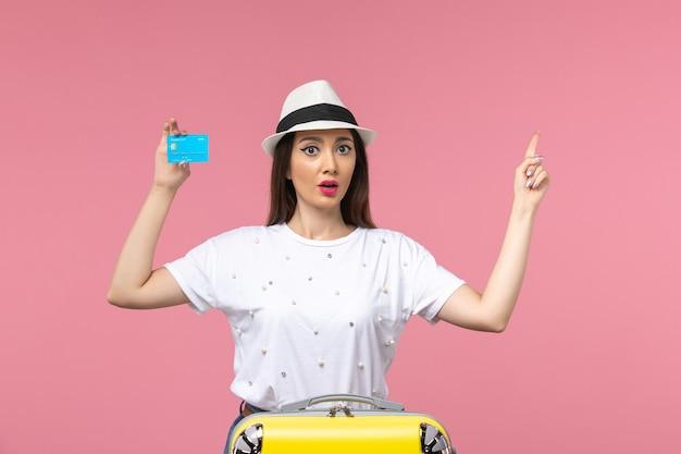 Mulher jovem segurando o cartão do banco na parede rosa claro de frente mulher viagem emoção de verão