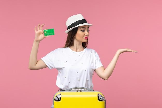 Mulher jovem segurando o cartão do banco na parede rosa emoção verão mulher de frente