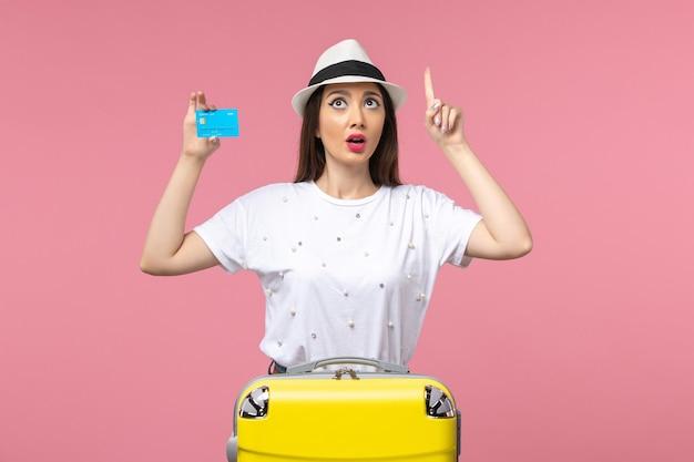 Mulher jovem segurando o cartão do banco na parede rosa emoções de verão mulher de frente
