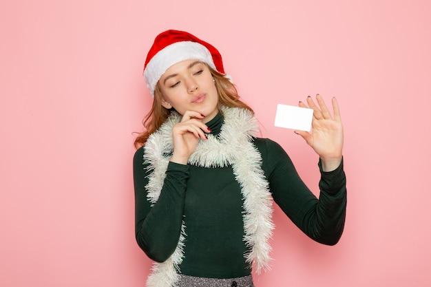Mulher jovem segurando o cartão do banco na parede rosa modelo de férias de ano novo de frente