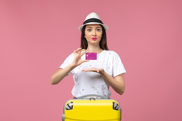 Mulher jovem segurando o cartão do banco na parede rosa mulher de férias dinheiro de frente