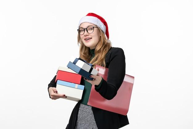 Mulher jovem segurando o feriado de frente, apresentando no livro de presente de piso branco, ano novo