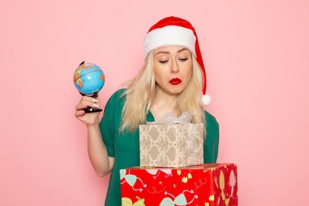 Mulher jovem segurando o globo e os presentes de natal na parede rosa foto modelo mulher cor de ano novo