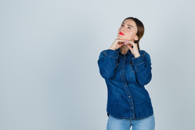 Mulher jovem segurando o queixo com uma camisa jeans e jeans e parecendo pensativa