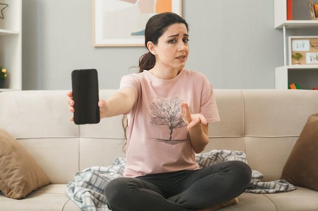 Mulher jovem segurando o telefone para a câmera, sentada no sofá, atrás da mesa de centro na sala de estar