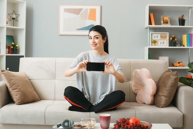 Mulher jovem segurando o telefone, sentada no sofá, atrás da mesa de centro da sala de estar