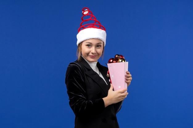 Mulher jovem segurando os brinquedos da árvore de frente na cor de emoção do feriado de ano novo de fundo azul