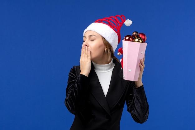 Mulher jovem segurando os brinquedos da árvore de frente no fundo azul, emoção azul, feriado de ano novo