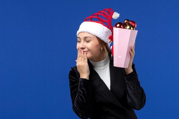 Mulher jovem segurando os brinquedos da árvore de frente no fundo azul emoção, feriados de ano novo