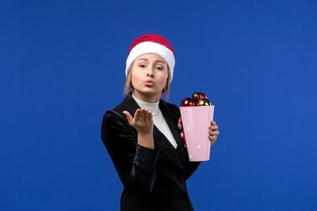 Mulher jovem segurando os brinquedos da árvore de frente para a cor de fundo azul nas emoções do feriado de ano novo