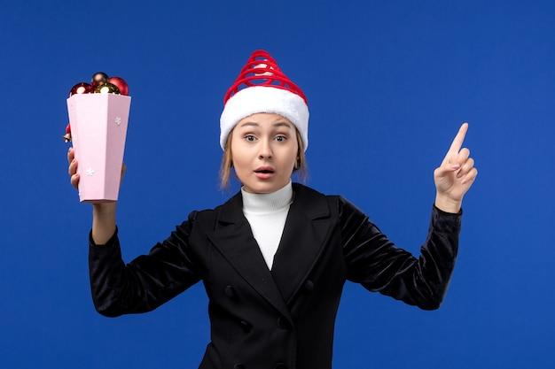 Mulher jovem segurando os brinquedos da árvore de frente para o fundo azul, cor de mulher do feriado de ano novo