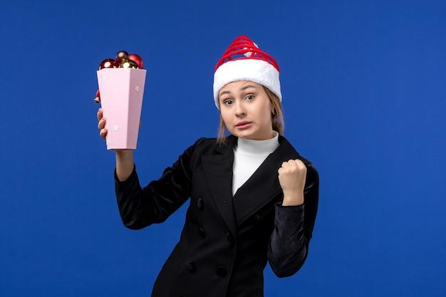 Mulher jovem segurando os brinquedos da árvore na mesa azul, mulher, feriado de ano novo, de frente