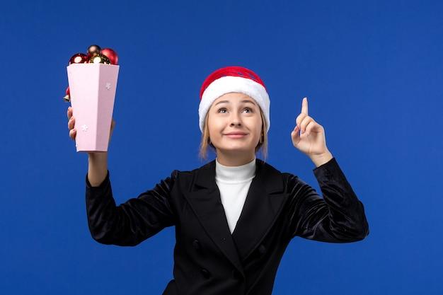 Mulher jovem segurando os brinquedos da árvore na mesa azul, vista frontal, ano novo, mulher, feriado, azul