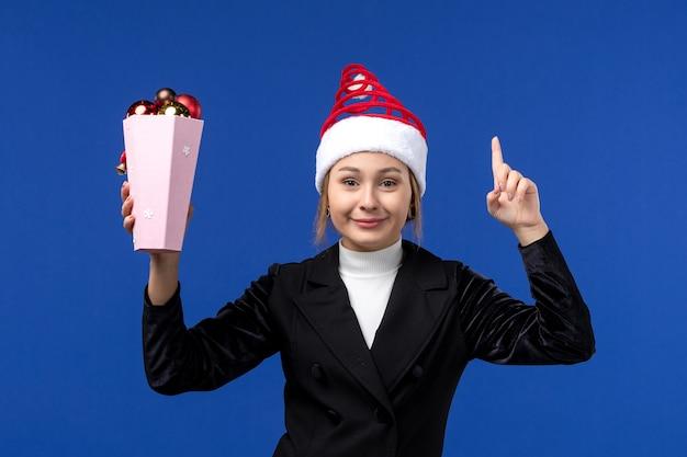 Mulher jovem segurando os brinquedos da árvore na parede azul-claro, mulher, feriado de ano novo, de frente, azul