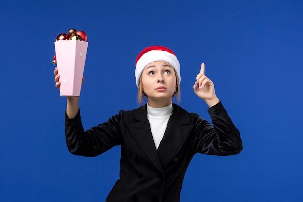 Mulher jovem segurando os brinquedos da árvore na parede azul mulher de férias de ano novo de frente
