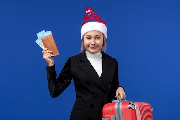 Mulher jovem segurando os ingressos com a bolsa no fundo azul, mulher, férias, vista frontal