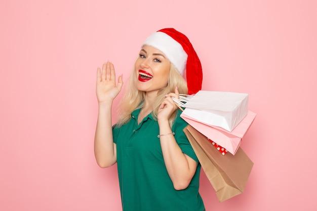 Mulher jovem segurando os presentes de natal em pacotes na parede rosa modelo de natal