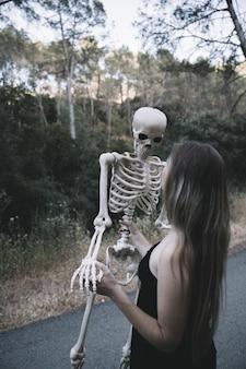 Mulher jovem, segurando, ossos