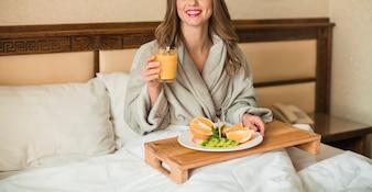 Mulher jovem, segurando, prato, frutas, e, suco laranja, ligado, madeira, bandeja